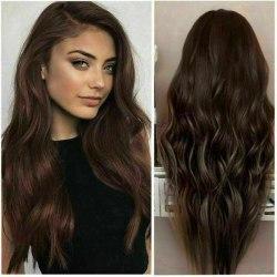 Kvinnans stora vågiga långa lockiga hår